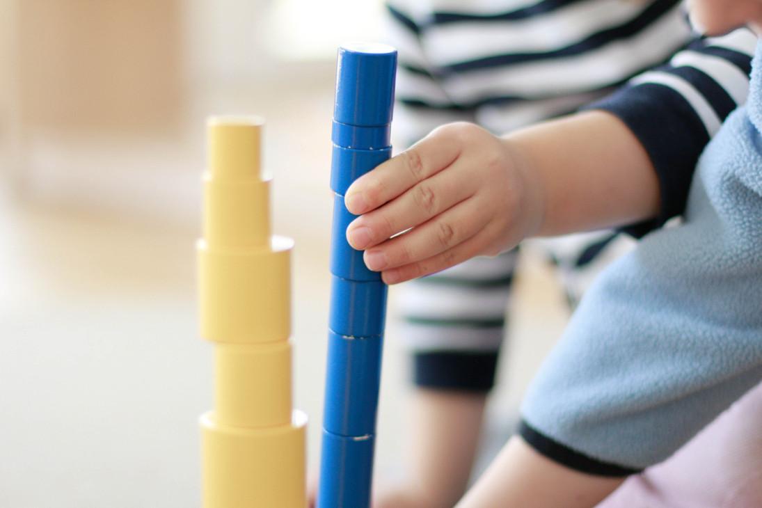 Zwei Kinder bauen Türme aus Montessori Material