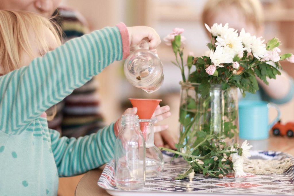 Ein Kind befüllt eine Vase in der Montessori Krippe Lüneburg