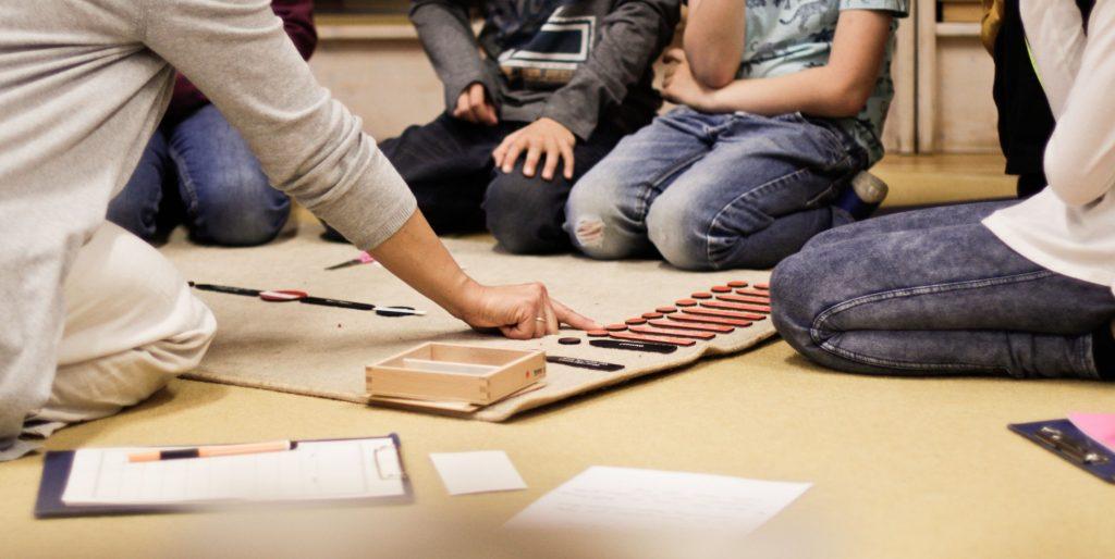 Eine Lehrerin der Montessori Schule zeigt in einer Darbietung die Arbeit mit Wortsymbolen