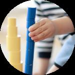 Kinder arbeiten mit den farbigen Zylindern im Montessori Kinderhaus Lüneburg